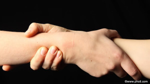 Assistência no exterior: um mão puxando um braço no sentido de apoio